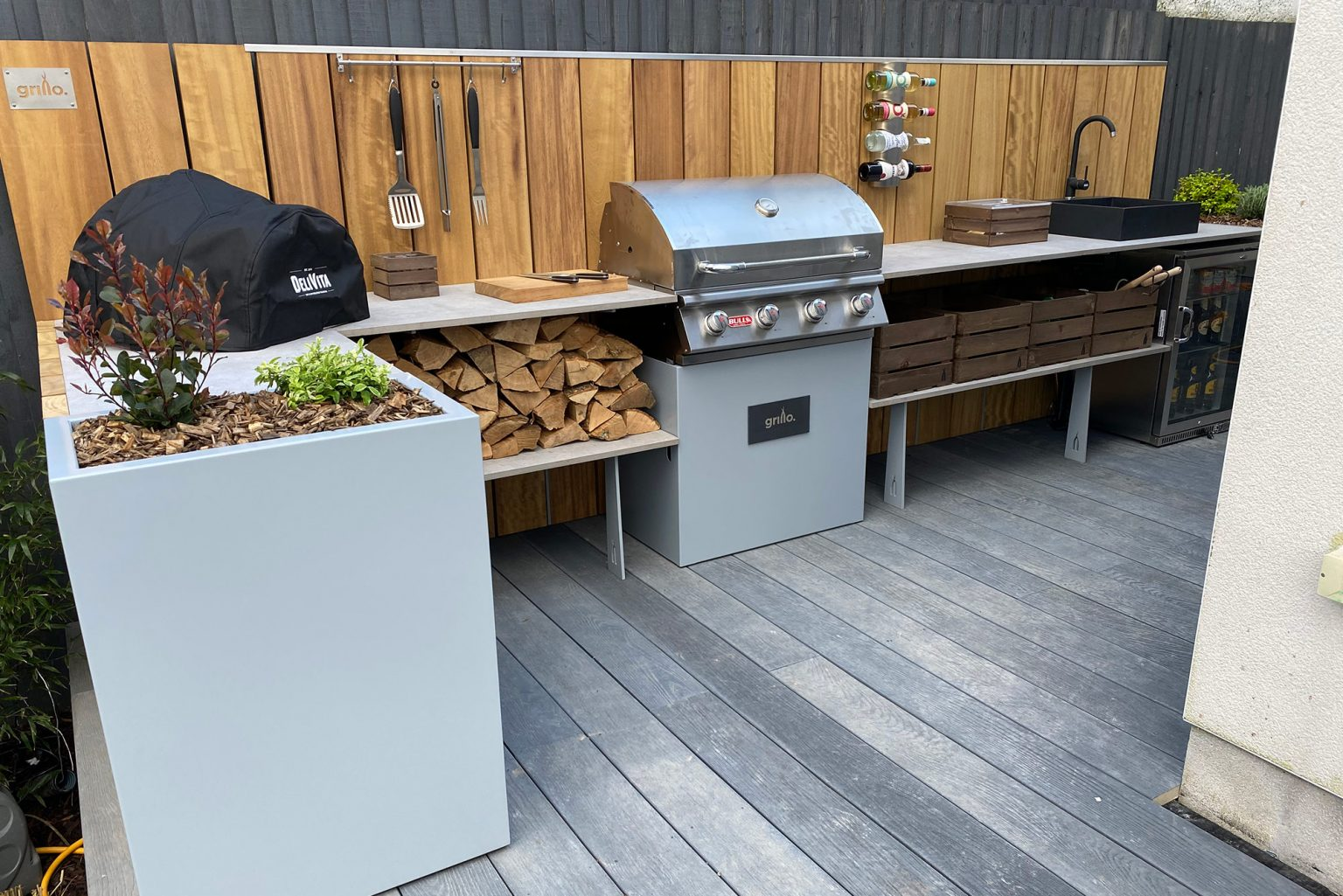 Small L shaped Grillo kitchen with planters, Delivita, Bull BBQ, sink, fridge, logs and storage crates
