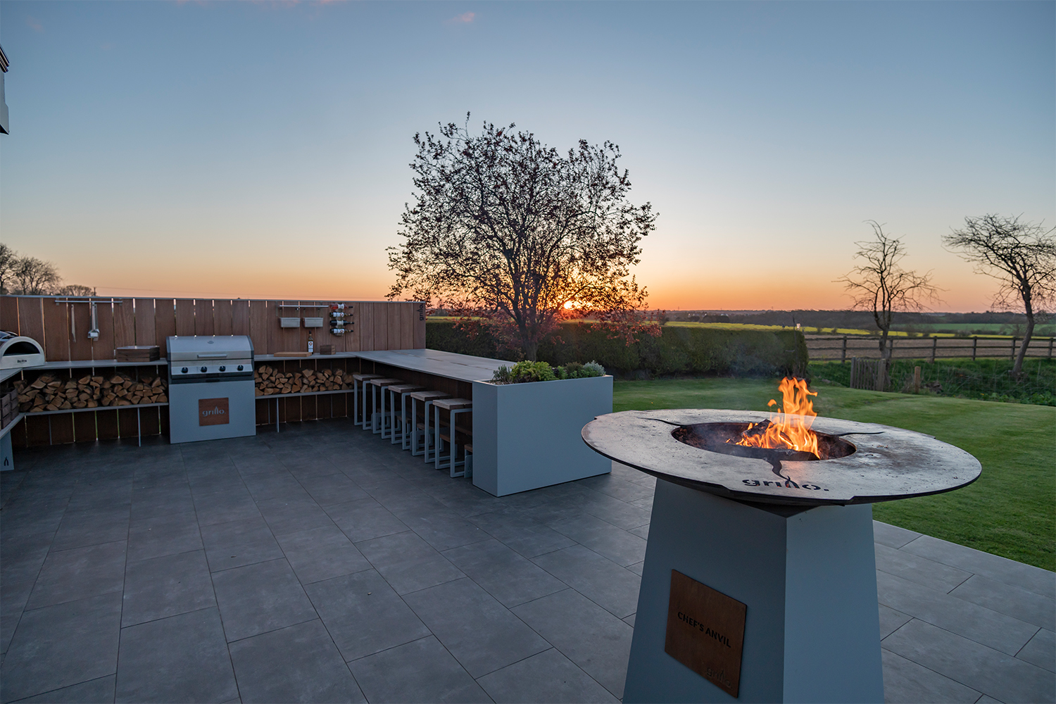 Grillo U shape kitchen with anvil lit, bar seating, planters, Delivita pizza oven, Cadac grill sunset in background