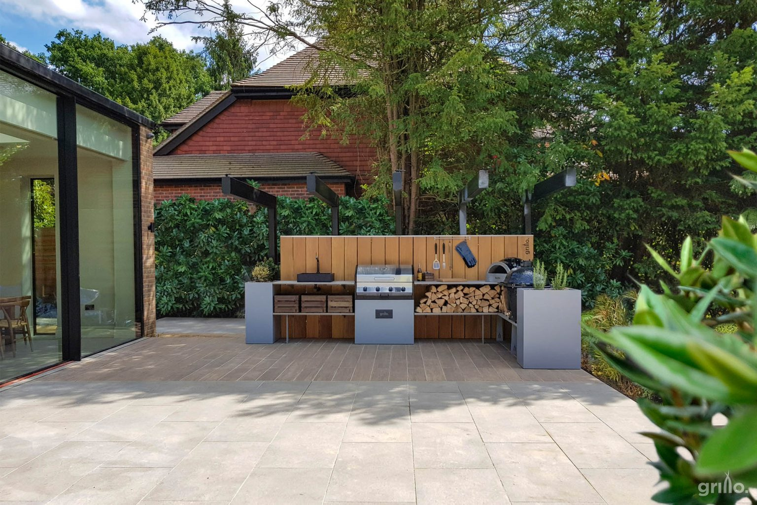 L shaped Grillo kitchen with Delivita, gas BBQ, storage crates logs, sink, planters and Primo