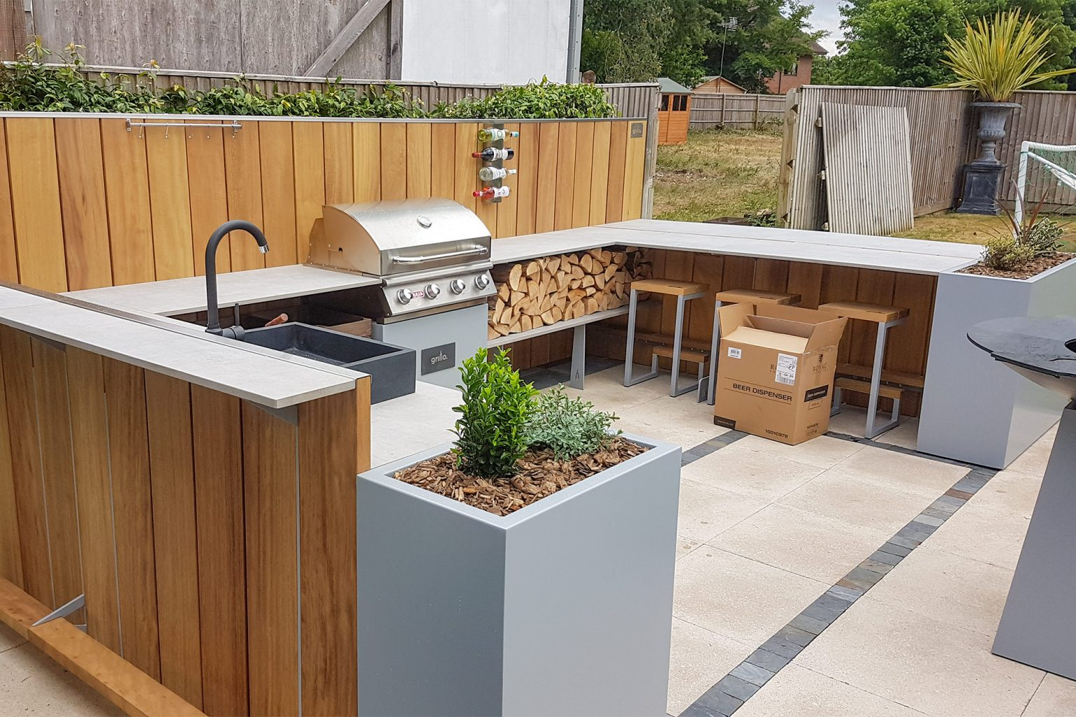 U shaped Grillo kitchen anvil with pub like standing bar, planters, anvil, sink, Gas BBQ, seating area, logs