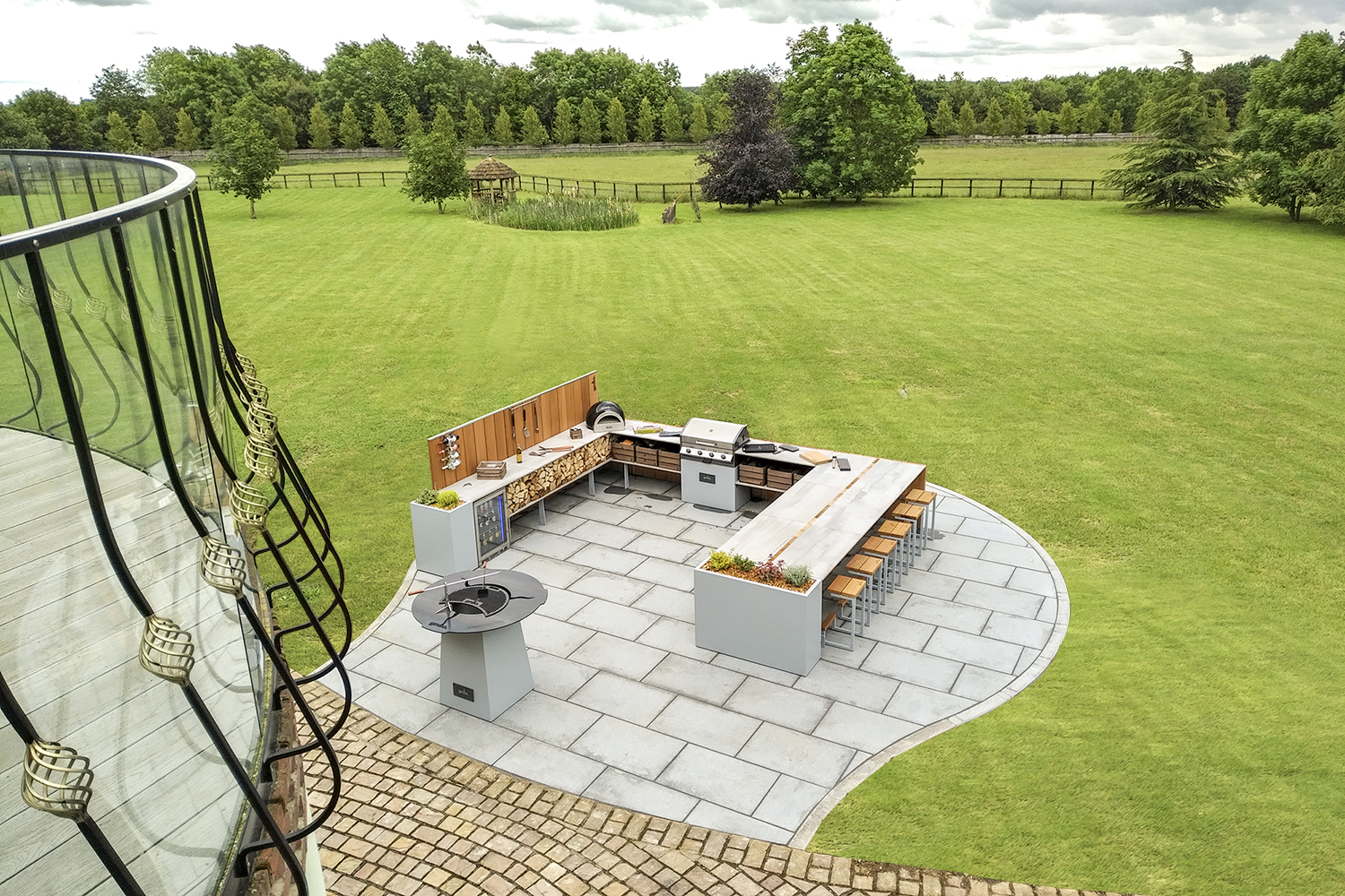 a large U shape Grillo Kitchen with under counter fridge, Logs, storage crates, Delivita, Cadac bar seating, planters, chefs anvil view from balcony