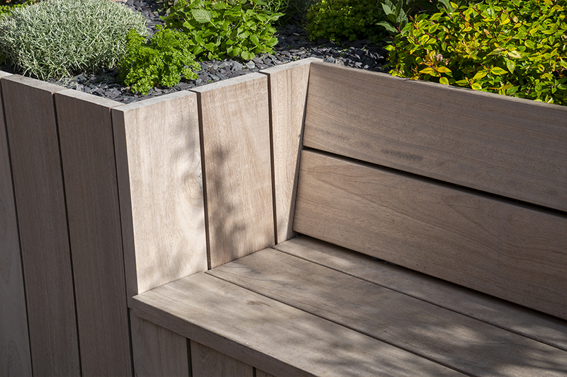 close up Grillo Outdoor Kitchen bench iroko wood and shrubs
