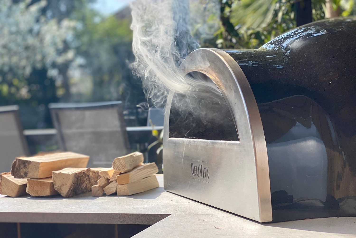 outdoor kitchens with pizza ovens close up of a smoking Delivita pizza oven