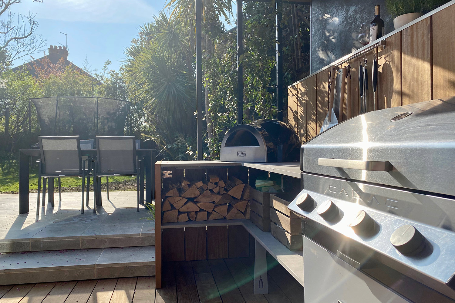 Chiswick project a shallow L forge Cadac pizza oven and under counter log storage