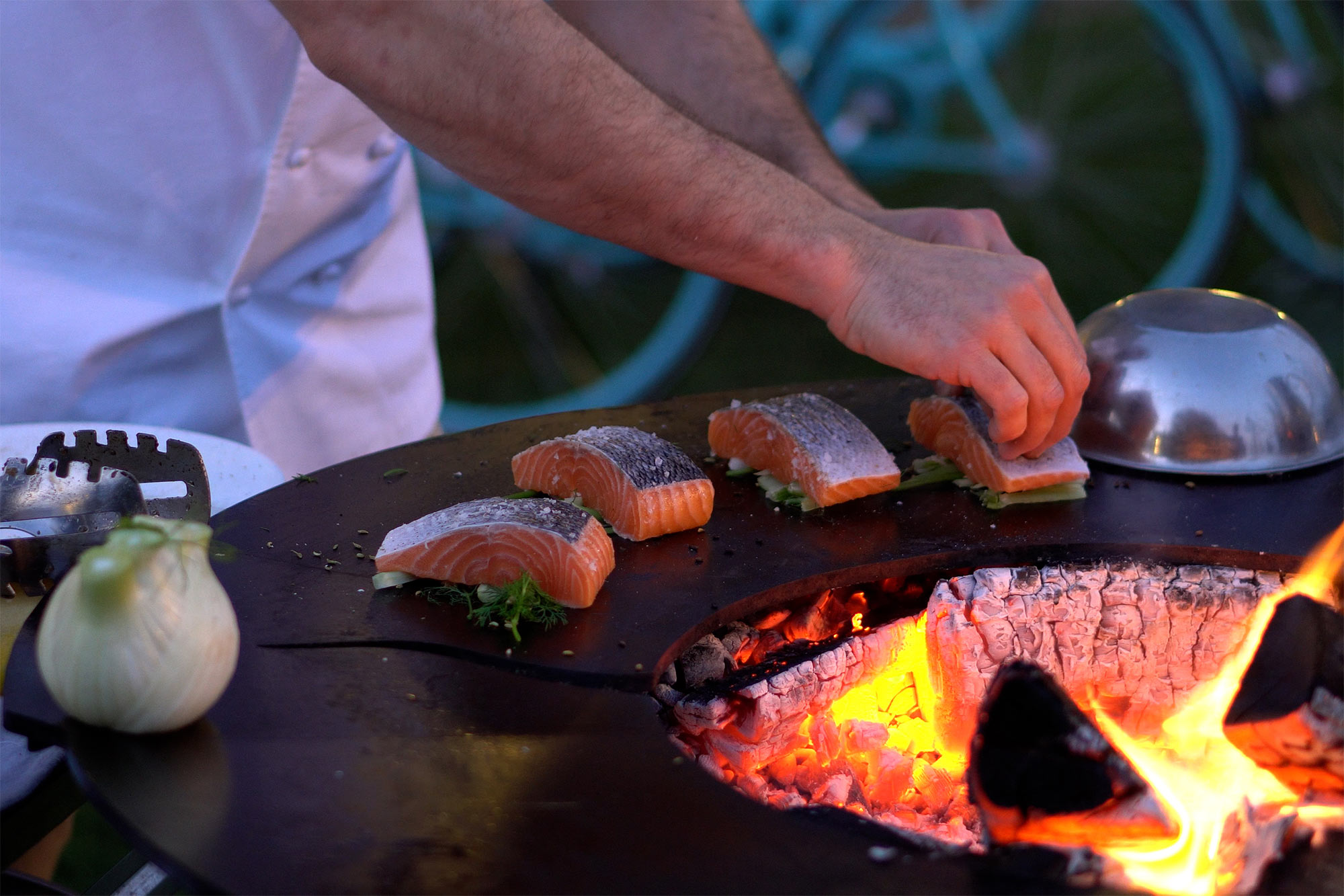 Chef cooking salmon on a chef's Anvil hotplate
